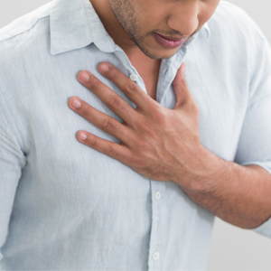 Man holding chest from burning sensation caused by GERD (acid reflux).